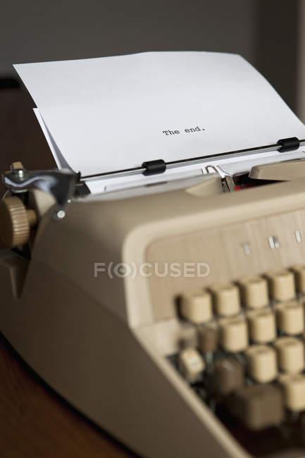 КОНЕЦ, напечатанный на листе бумаги на винтажной пишущей машинке — стоковое фото