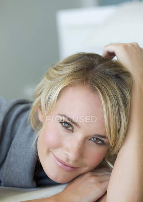 Retrato de uma jovem mulher deitada em uma cama — Fotografia de Stock