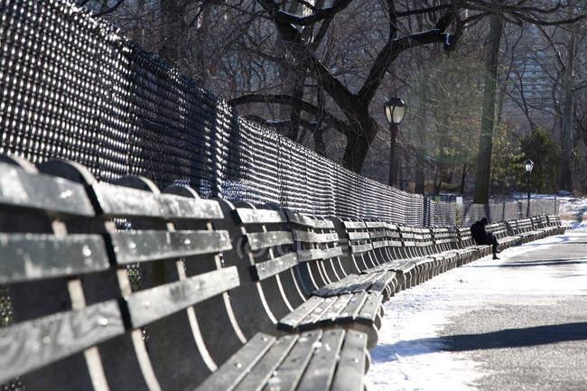 Отдаленный взгляд на человека, сидящего на скамейке в парке зимой — стоковое фото
