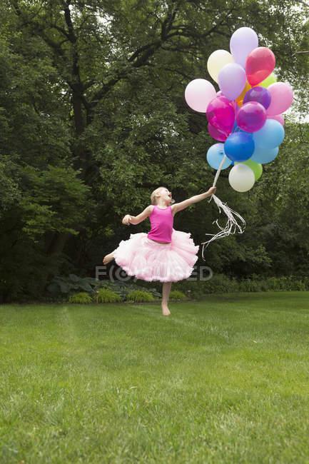 Niña juguetona saltando mientras sujeta los globos en el patio trasero - foto de stock