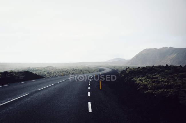Curvy country road at foggy mountain valley against clear sky — Stock Photo