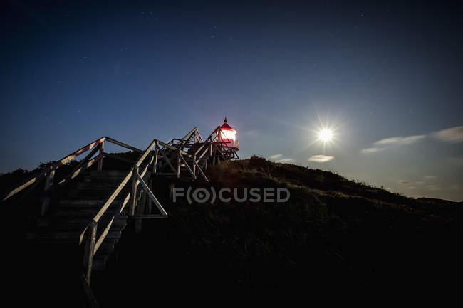Étapes menant au phare illuminé au-dessus du ciel du crépuscule — Photo de stock