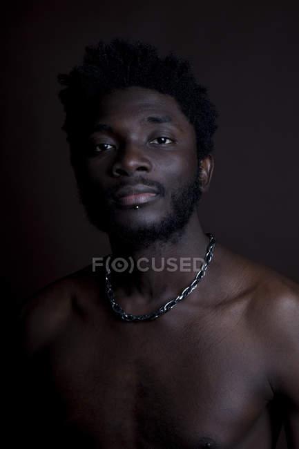 Un uomo senza camicia che guarda pensieroso nella macchina fotografica — Foto stock