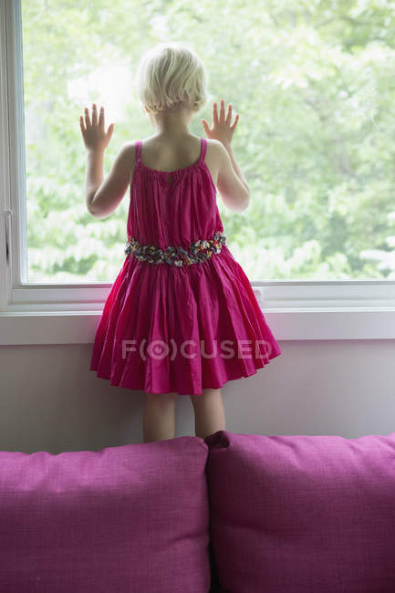 Rear view of girl standing on sofa by window at home — Stock Photo