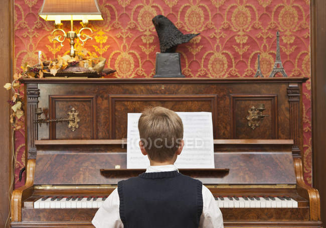 Rear view of boy practicing on upright piano — Stock Photo