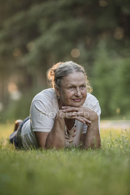 Thoughtful senior woman lying on grass in park — Stock Photo