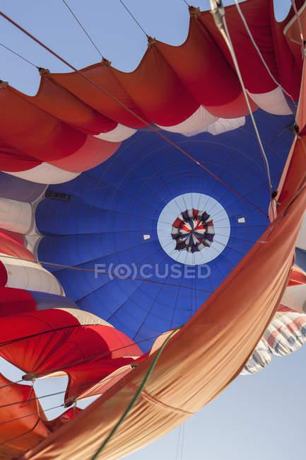 Vista inferior del globo de aire caliente contra el cielo - foto de stock