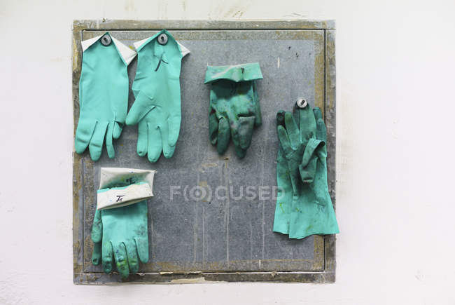 Green gloves hanging on wall in factory — Stock Photo