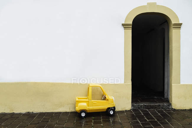 Yellow toy car parked by building doorway — Stock Photo