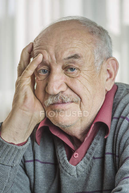 Portrait of worried senior man with hand on face at home — Stock Photo