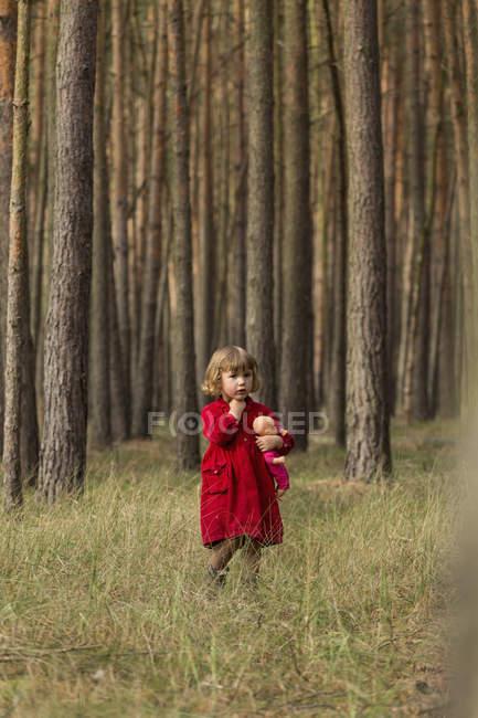 Menina olhando para longe, mantendo a boneca na floresta — Fotografia de Stock
