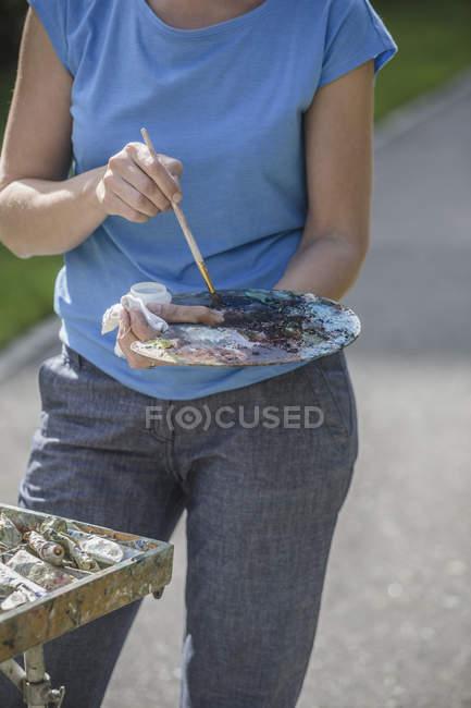 Milieu du peintre femelle tenant le pinceau et la palette dans le parc — Photo de stock