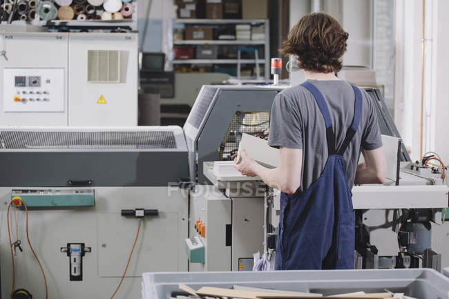 Rear view of young male worker operating machine in factory — Stock Photo