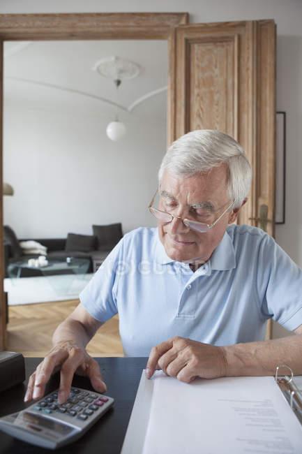 Senior man calculating home finances at table — Stock Photo