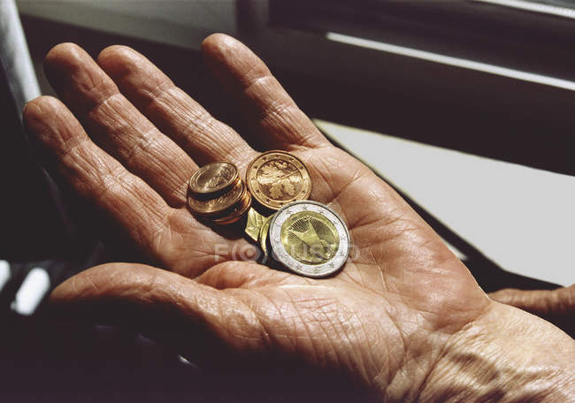 Mano femenina cultivo monedas de Euro - foto de stock