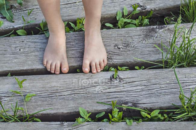Unterteil eines barfüßigen Kindes, das auf der Promenade steht — Stockfoto