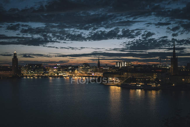Scenic view of waterfront and illuminated city against sky at dusk, Stockholm, Sweden — Stock Photo