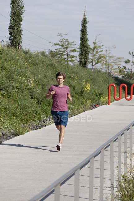 Mittlerer erwachsener Mann joggt auf Fußweg — Stockfoto