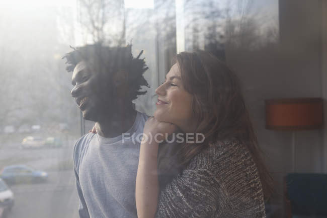 Счастливая любящая пара, выглядывающая в окно — стоковое фото