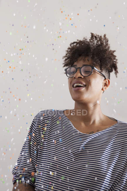 Happy young woman looking at confetti flying at home — Stock Photo