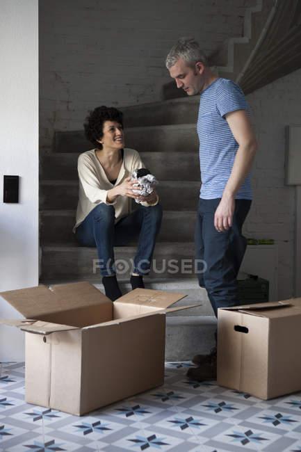 Emballage de couple mixte âge déplacez boîtes sur l'escalier à la maison — Photo de stock