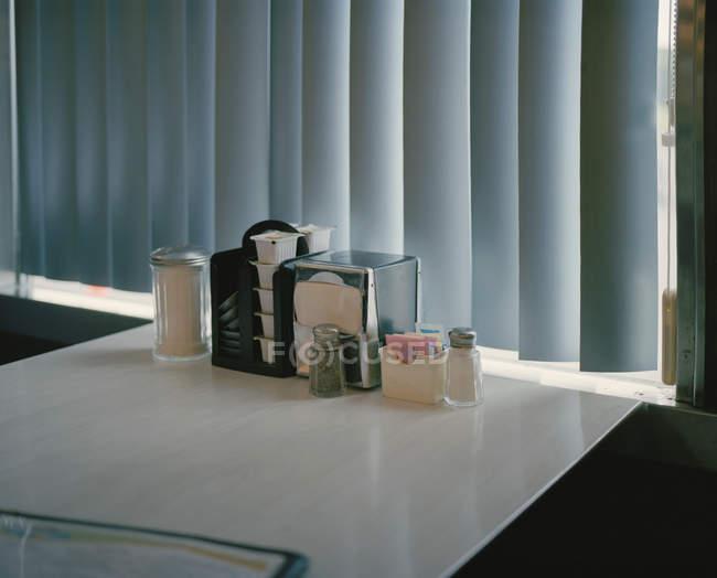 Gewürze auf leerem Esstisch durch zertrümmertes Fenster — Stockfoto
