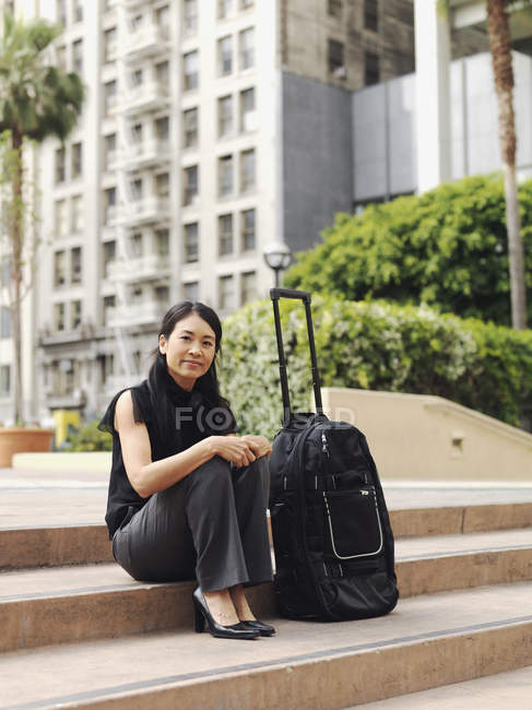 Businesswoman sitting on step outdoors next to rolling suitcase — Stock Photo