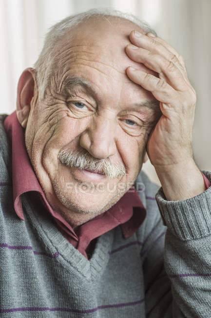 Retrato de homem sênior preocupado com a cabeça na mão em casa — Fotografia de Stock