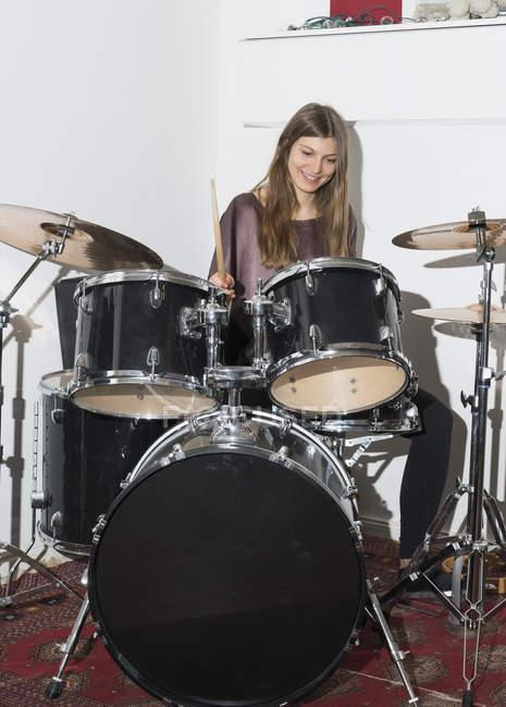 Felice giovane donna che suona la batteria — Foto stock