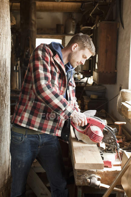 Man using circular saw on a plank in workshop — Stock Photo