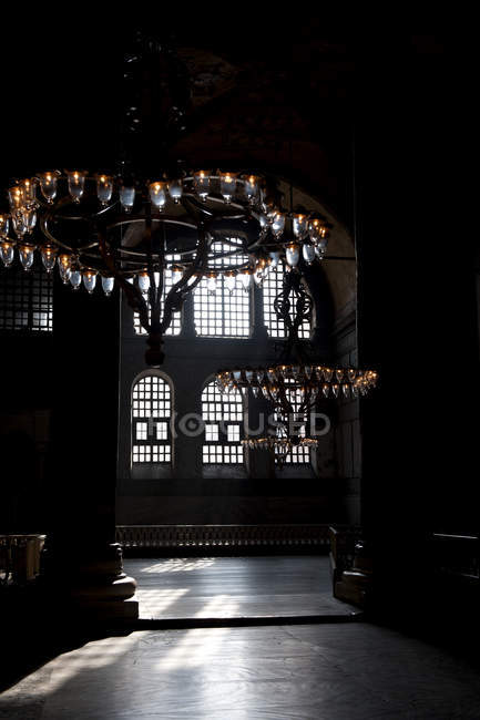 Chandeliers hanging in shadowed interior of Blue Mosque, Istanbul, Turkey — Stock Photo