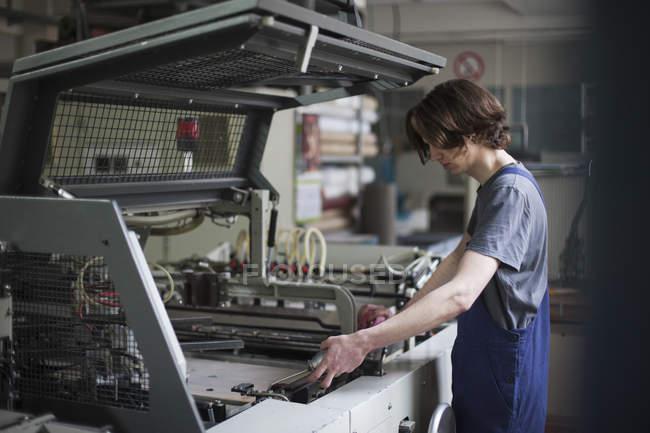 Máquina de aceite de trabajador manual joven en fábrica - foto de stock