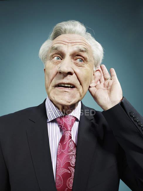 Senior homme avec la main derrière l'oreille sur fond bleu — Photo de stock