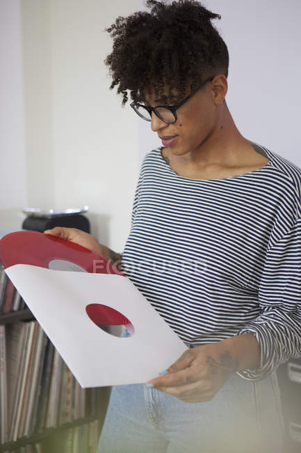 Young woman removing vinyl record from paper case at home — Stock Photo