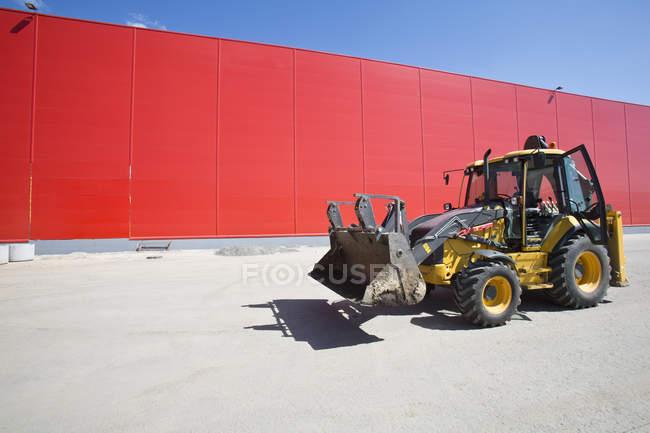 Бульдозер на стоянке рядом с склад красный фасад — стоковое фото