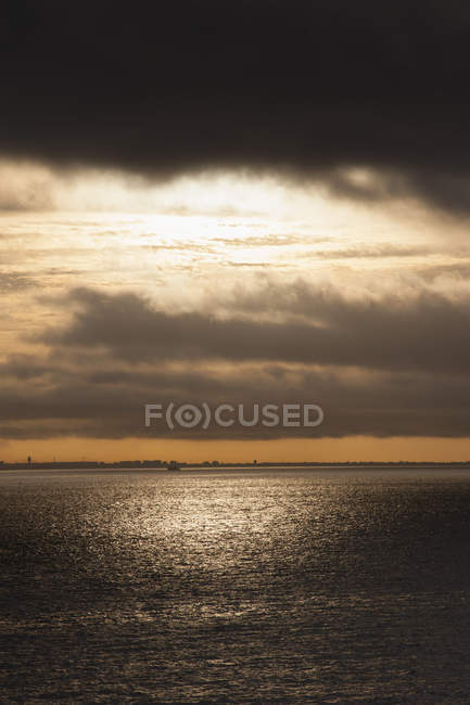 Scenic view of sea against cloudy sunset sky — Stock Photo