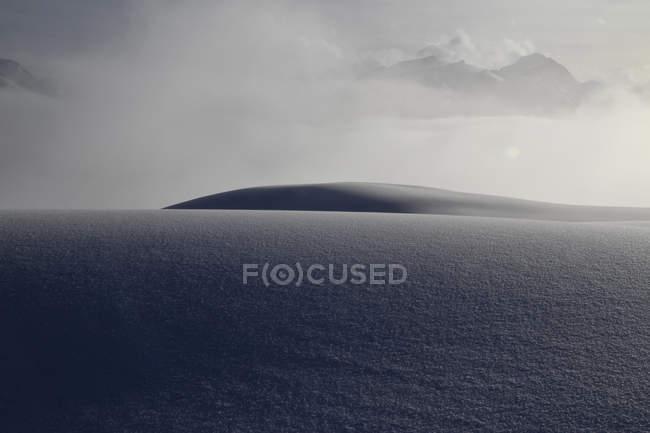 Manto de nieve con las montañas nubladas en fondo - foto de stock