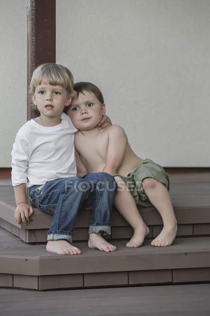 Longitud completa de chicos lindos mirando hacia otro lado mientras están sentados en el porche - foto de stock