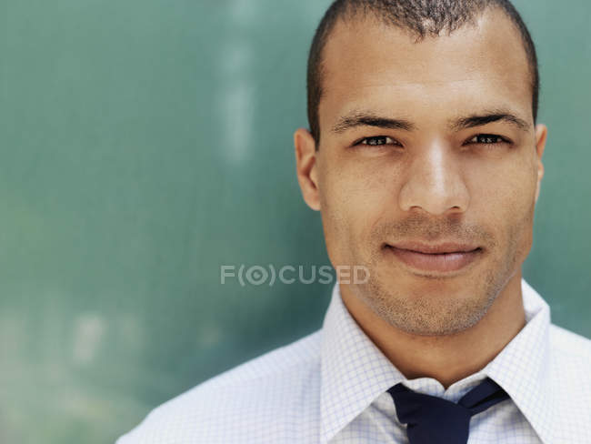 Portrait of smiling young businessman in front of green wall — Stock Photo