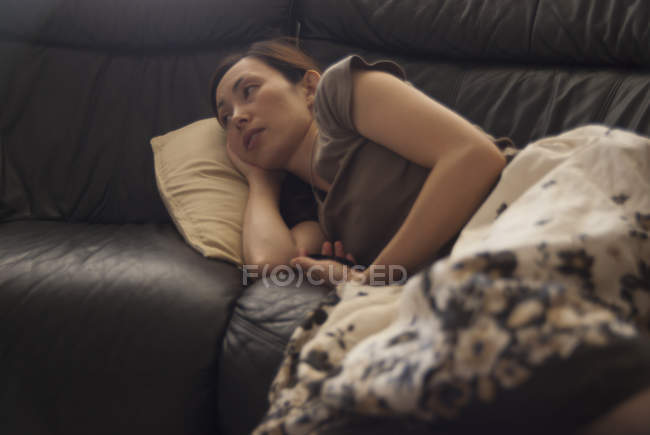 Pensive woman resting on sofa under blanket — Stock Photo