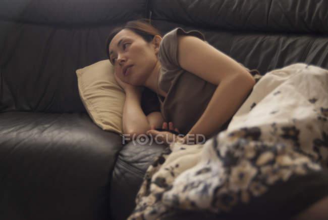 Замислений жінка, відпочиваючи на диван під ковдрою — стокове фото
