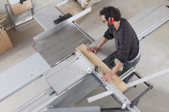 Carpenter using a sliding table saw in workshop — Stock Photo