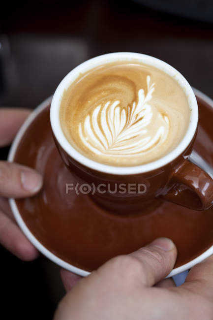 Crop barista's hands serving cappuccino with floral pattern in milk froth — Stock Photo