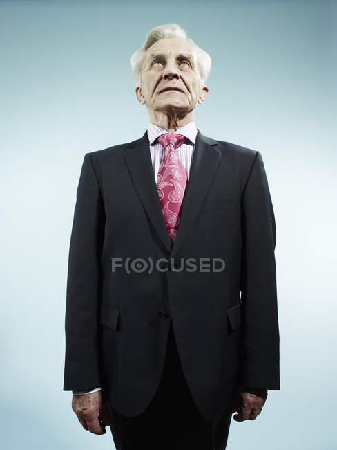 Élégant homme senior vêtu d'un costume et une cravate rose — Photo de stock