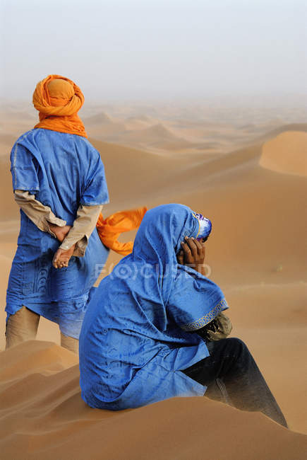 Marokkanische Männer gekleidet in traditioneller Kleidung an Dünen sitzen — Stockfoto