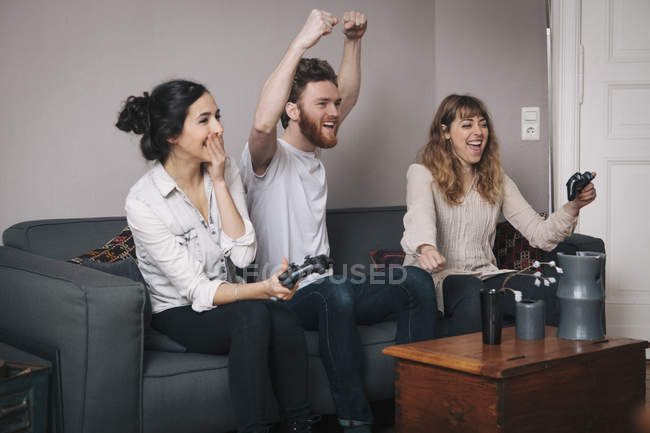 Excited young friends playing video games at home — Stock Photo