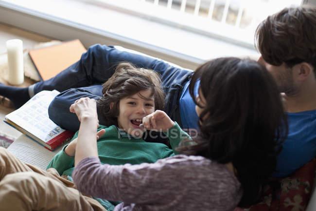 Мальчик, весело с родителями на диване у себя дома — стоковое фото