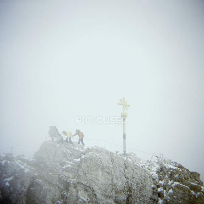 People hiking near crucifix on snowy mountain peak — Stock Photo