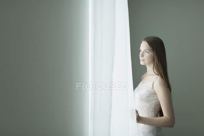 Jovem pensativa olhando através da janela em casa — Fotografia de Stock