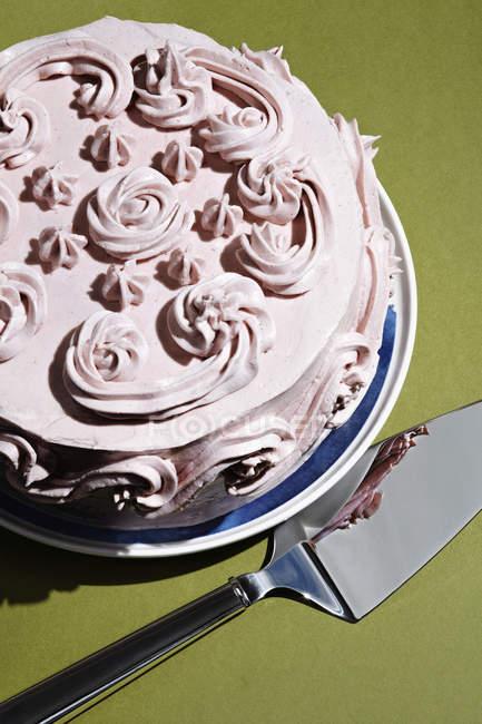 Vista de ángulo bajo de torta cremosa con espátula sobre tabla - foto de stock